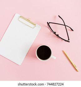 Minimal women home office desktop with clipboard, pen, coffee mug and glasses on pink background. Flat lay, top view blog header or hero.