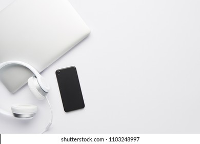 Minimal work space concept. Top view of laptop, white headphones and black cell phone on white background with copy space. Flat lay.