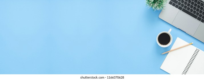 Minimal work space - Creative flat lay photo of workspace desk. Top view office desk with laptop, notebooks and coffee cup on blue color background. Panoramic banner background with copy space.