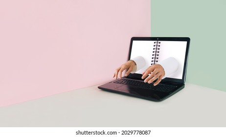 Minimal workspace made of laptop with notepad and male hands typing on keyboard. Back to school during the covid-19. Virtual surreal distance learning scene on pastel beige, green and pink background.
