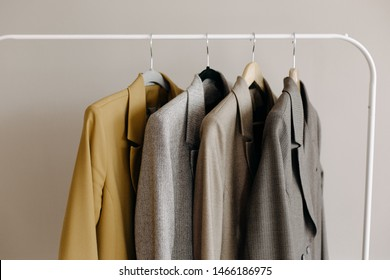 Minimalism concept. Coats on the rail on beige background