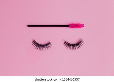 Minimalism false eyelashes with brush for combing on pink background. Copy space beauty fashion.