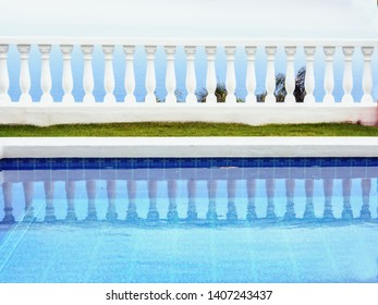 Minimalism of form and color, a terraced with white space, In front of it, the section of a water basin with the reflection of the columns in the water.
