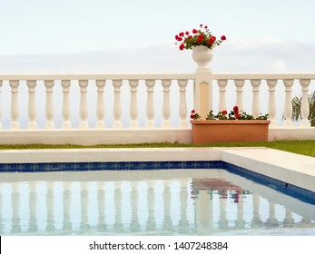 Minimalism of form and color, a terraced white space with a white pot with dark red geraniums against whitish sky. In front of it, the section of a water basin with the reflection