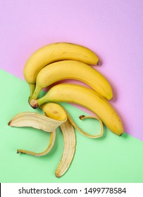 Minimalism fruit concept. Bunch of bananas and banana skin on pastel background. Top view