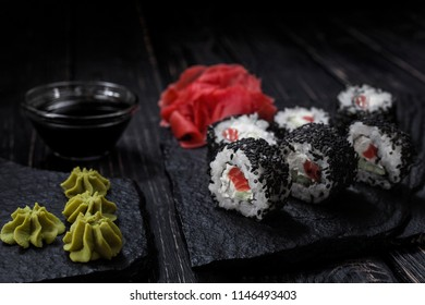 Minimalism and refinement: Tasty sushi with salmon and avocado are covered with black sesame seeds. Served with Ginger and Wasabi on the black stone.