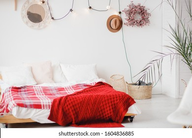 Minimalism Scandinavian style bedroom with white walls and garland on wall with room palm.