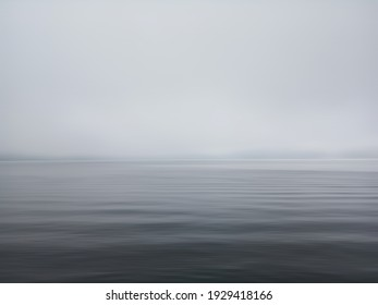 Minimalism scene of misty morning background in the sea. Fog over lake wave water. Calm beach view. Tranquil empty landscape with soft blue gray gloomy sky. Nature abstract art backgrounds. Copy space