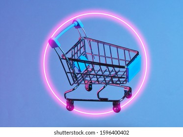 Minimalism shopping concept. Toy shopping trolley, circle neon night. Retro wave