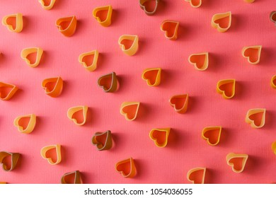 Minimalism style. Repetition concept. View from above on pasta pattern with heart shape, on colored background.