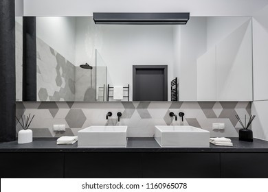 Minimalist bathroom in black, grey and white with two basins and big mirror