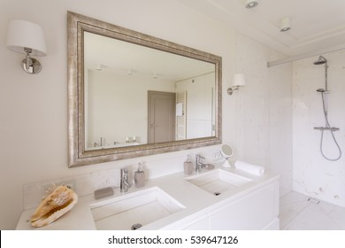 Minimalist bathroom with large mirror in a decorative frame and two marble sinks