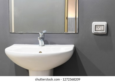 Minimalist  bathroom with sink and  square mirror hanging on a grey  wall