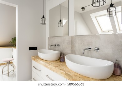Minimalist bathroom with two sinks and wooden vanity top