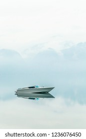 Minimalist boat on the lake with symmetrical reflection of the clouds. Attersee lake in Austria