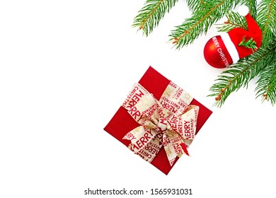 Minimalist Christmas background with gift, fir branches and decorations over white background