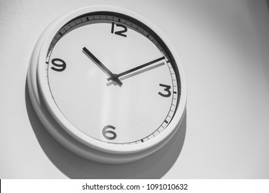 Minimalist Clock or Simple white clock hang on white wall with space for text.
