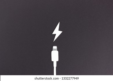 Minimalist composition of paper cable and icon of charging on black background