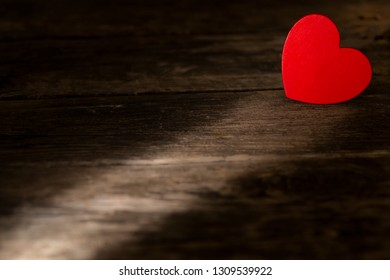 Minimalist composition of red heart lying on wooden table in beam of sunshine