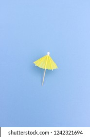 Minimalist composition of yellow cocktail umbrella on blue background