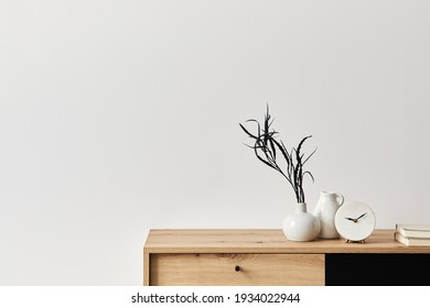 Minimalist concept of living room interior at elegant apartment with wooden commode, leaf in ceramic vase, clock and elegant personal accessories in modern home decor. Copy space. Template. .