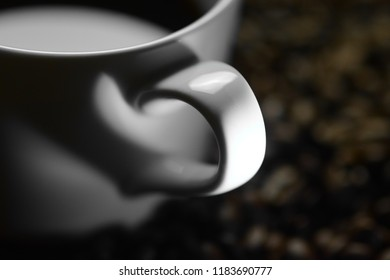 Minimalist concept with shadow depicting love for coffee - The handle's shadow of a cup in the coffee and which stands on coffee beans looks like a heart in the shadow of light