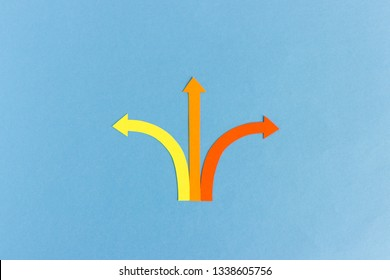 Minimalist cutout composition of yellow, red and orange arrows showing three different directions on blue background
