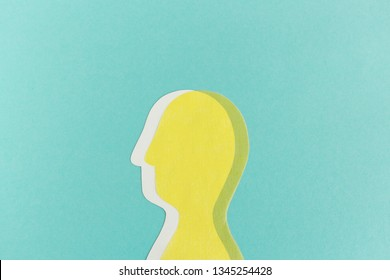 Minimalist cutout of double paper man on blue background