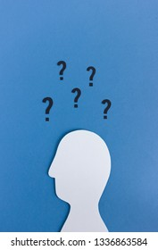 Minimalist cutout of white paper man with question marks above head on blue background