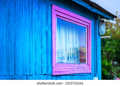 Minimalist Design Concept: Vivid Purple Window Frame, a Light on Blue Wall of Wooden Planks. Mountains Reflection in Glass, White Curtain. Roof Eaves. Garden Trees