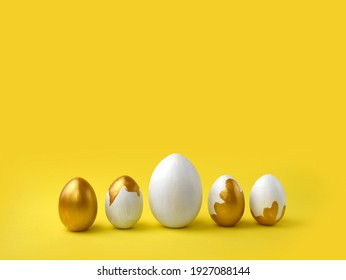 Minimalist Easter composition. Golden paint pouring eggs in row on yellow background. Greeting trendy color concept with copyspace.