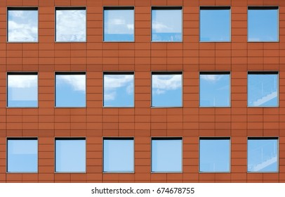 Minimalist facade of modern office building with square Windows. Finish is a dark red color. The details of the architecture of the urban landscape