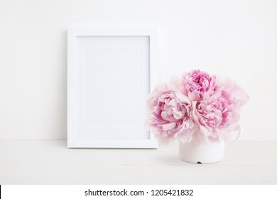 minimalist female mock up with white photo / picture frame and beautiful pink peonies in an enamel mug on a white desk, portrait format