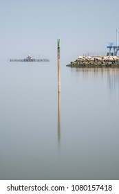 Minimalist fine art image of lifeguard tower in juxtaposition with old derelict pier in background