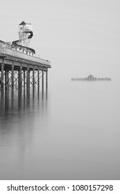 Minimalist fine art image of new pier in juxtaposition with old derelict pier in background in black and white