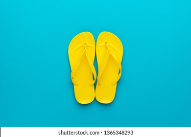 minimalist flat lay photo of pair of yellow beach flip-flops on the blue background summer concept