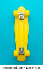 minimalist flat lay photo of yellow plastic mini cruiser board on blue background. top view of bright yellow cruiser skateboard