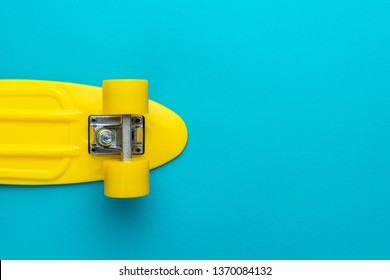 minimalist flat lay photo of yellow plastic mini cruiser board on blue background. top view of bright yellow cruiser skateboard with copy space