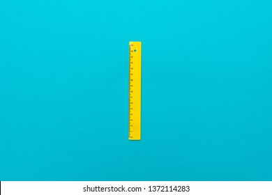 minimalist flat lay photo of yellow plastic ruler on the turquoise blue background. top view of plastic ruler with central composition.