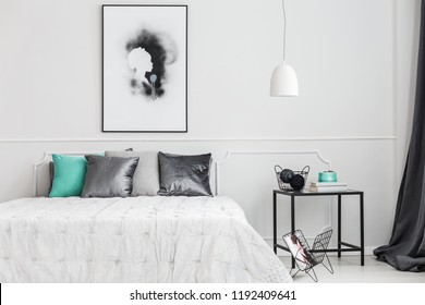 Minimalist, framed poster mock-up on a white wall of an artistic bedroom interior with elegant decor and gray textiles