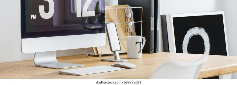 Minimalist graphic designer's modern, wooden desk with computer close-up