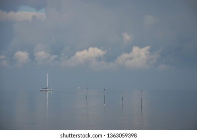 Minimalist image of a hazy day at Oosterschelde estuary, the Netherlands with a little sailing yacht, dramatic clouds, and wooden poles