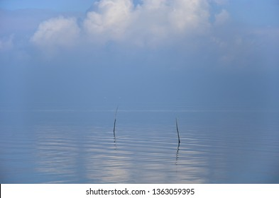Minimalist image of two wooden sticks in a smooth water surface under a dramatic cloud on a hazy day at Oosterschelde estuary, the Netherlands