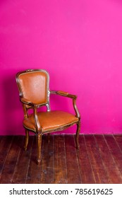 Minimalist interior with armchair, pink wall and wooden floor. Copy space for text.