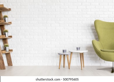 Minimalist interior with white brick wall and olive green upholstered egg chair