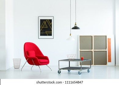 Minimalist Living Room Interior With A Movable Coffee Table, Red Armchair,  Lamps And Paintings