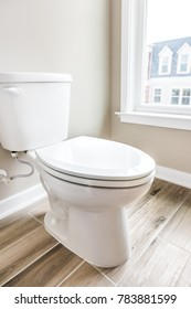 Minimalist modern clean white toilet in restroom with window in model house, home or apartment