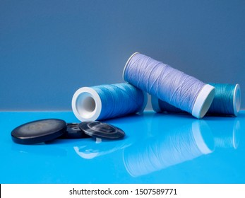 Minimalist modern sewing image in blue colors. With blue spools of thread, buttons and a blue background.