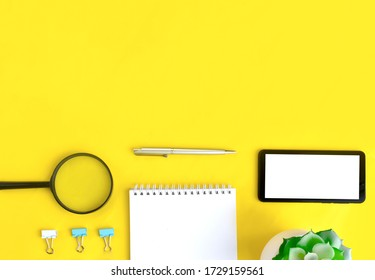 Minimalist office flat lay with mobile phone, magnifying glass, notebook and succulent on yellow background. Job searching or distance learning  concept. Banner with copyspace.
