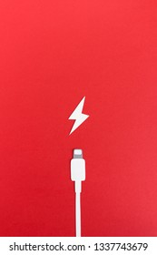 Minimalist paper composition of battery charging wire and icon of thunder on red background